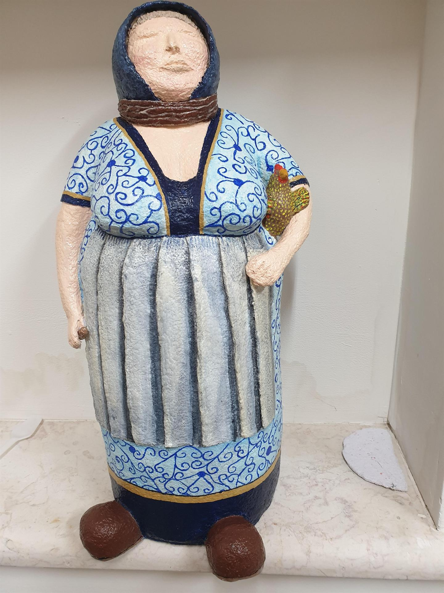 פסל אישה עם תרנגולת מעיסת נייר של כוכבה