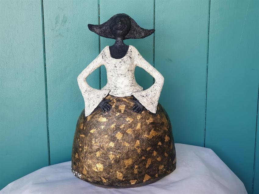 הסטודיו של אדוה - שלבי הכנת פסל מעיסת נייר של נערה בחצאית עם עיטור בעלי זהב.