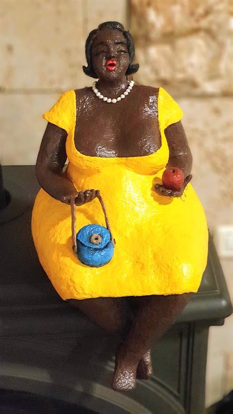 הסטודיו של אדוה - שלבי הכנת פסל מעיסת נייר: אשה יושבת עם שמלה צהובה ותיק קטן.